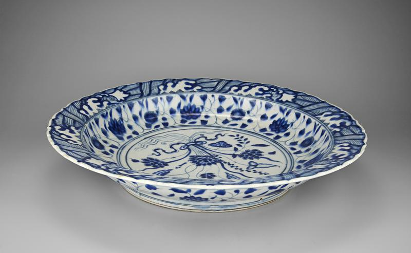 A blue and white floral-patterned dish following a Chinese model so closely that it might have passed for a Chinese original if the body had been translucent like porcelain. Blue and white designs cover the white plate with a foliage design in the centre.