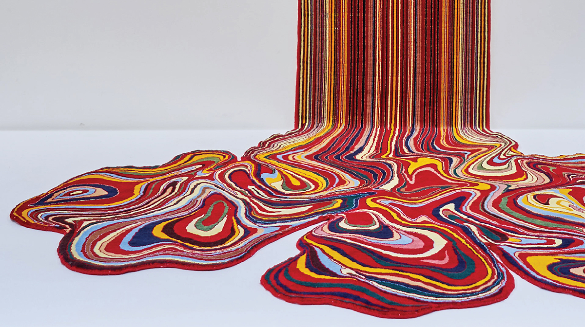 A painting-like sculpture with bright colours, including blue, red, and yellow, appears to ooze down a wall and swirl together on a white floor.