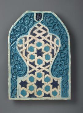 Blue, teal and white panel in the form of a mihrab arch delicately carved in high relief enclosing an inner trefoil palmette standing on a short waisted foot.