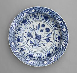 Blue and white dish with sloping foliate rim, in the centre a lotus bouquet tied with a ribbon.