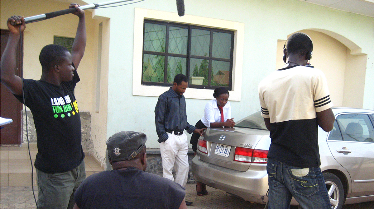 A film crew shoots a scene featuring two actors in the driveway of a house beside a Honda Accord.