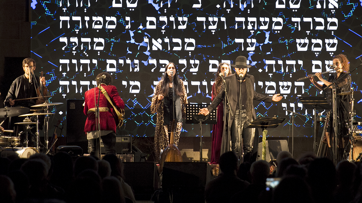 The band Yemen Blues performs against a backdrop of Hebrew writing on the stage's back wall.
