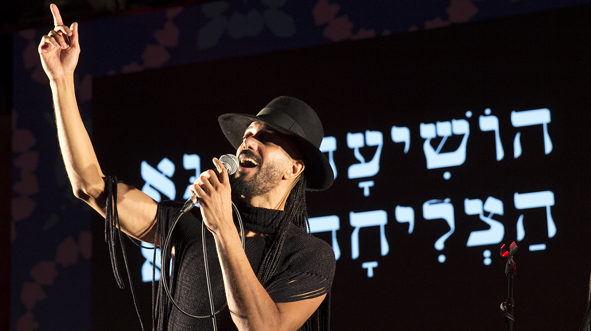 Frontman Ravid Kahalani points upwards as he sings on stage, against Hebrew writing in the backdrop.