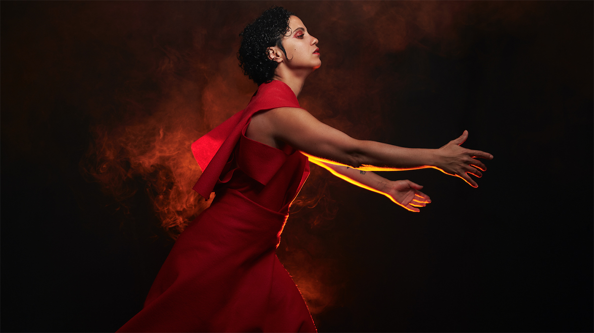 Emel Mathlouthi in profile, wearing a red dress and leaning forward with arms extended, against a dark background and red smoke.