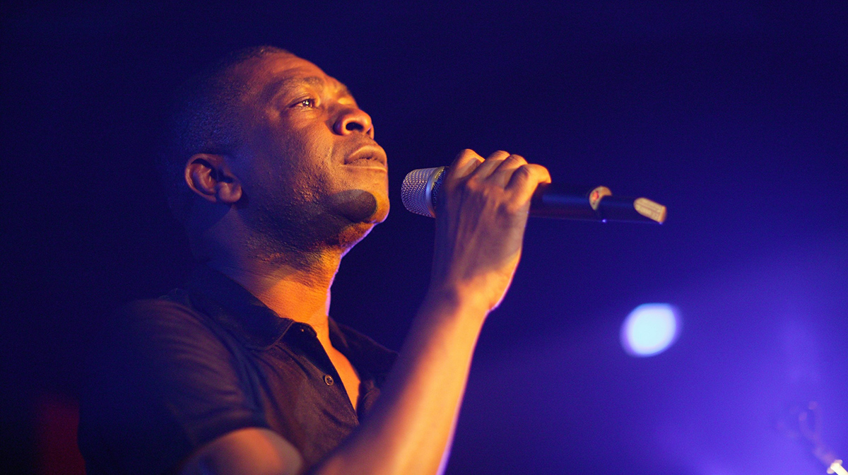 Youssou N'Dour sings passionately into a microphone against a navy backdrop.