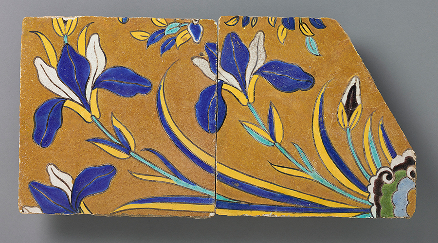 Two ceramic tiles from 17th-century Iran painted with a blue, yellow, and green floral pattern.