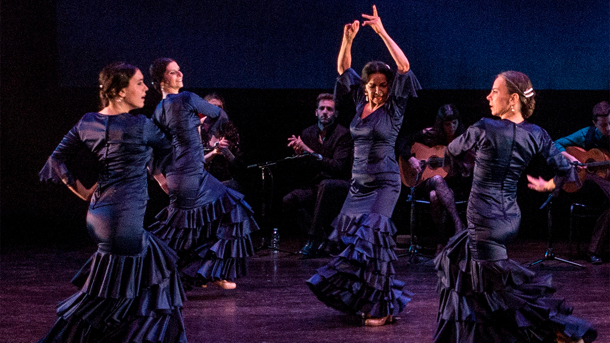 A troupe, wearing blue ruffled dresses, dance Flamenco on stage.