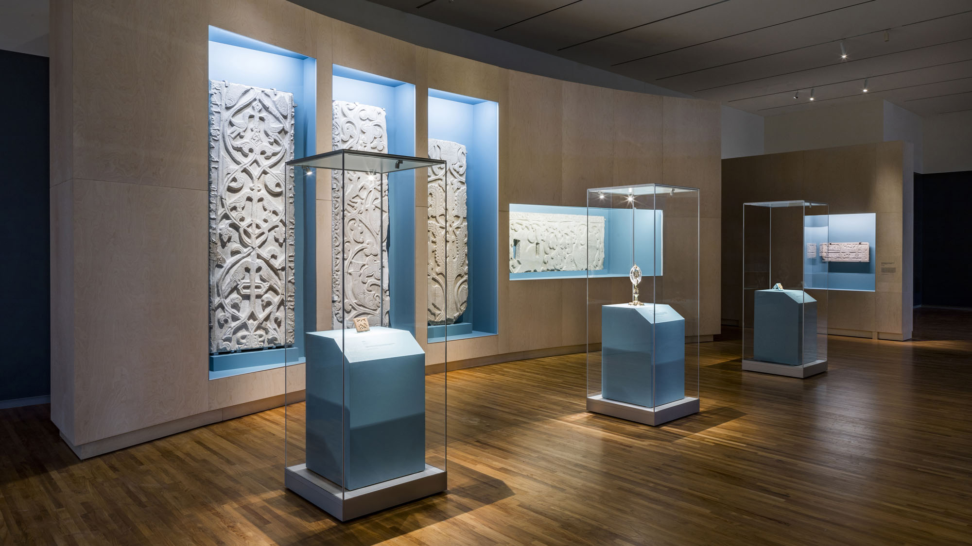 Three glass cases, each one containing a 1,000-year-old artifact from the Fatimid Caliphate, stand in front of a wall-mounted glass case containing segments of engraved stone walls.